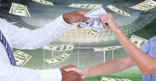 Midsection van mensen die handen schudden terwijl het overgaan van geld bij voetbalstadion die corruptie vertegenwoordigen stock foto's