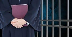 Midsection van rechter met boek tegen gevangenis royalty-vrije stock afbeelding