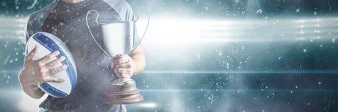 Midsection van succesvolle de holdingstrofee en bal van de rugbyspeler royalty-vrije stock afbeelding
