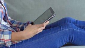Midsection van vrouw die digitale tablet op bank gebruiken stock videobeelden