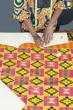 Midsection van vrouwelijke manierontwerper die patroon met krijt op stoffentextiel merken Stock Afbeeldingen