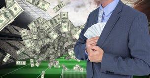 Midsection van zakenman verbergend geld bij voetbalstadion die corruptie vertegenwoordigen royalty-vrije stock fotografie