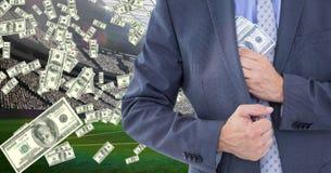 Midsection van zakenman verbergend geld bij voetbalstadion die corruptie vertegenwoordigen stock foto's