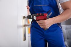 Man Installing Door Knob With Wireless Screwdriver. Midsection View Of A Man`s Hand Installing Door Knob With Wireless Screwdriver royalty free stock images