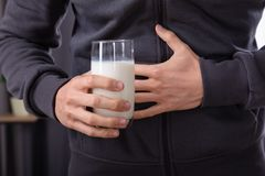 Man Having Stomach Pain Holding Glass Of Milk. Midsection View Of A Man Suffering From Stomach Pain Holding Glass Of Milk royalty free stock photos