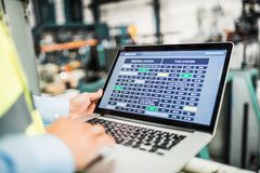 A midsection of an industrial man engineer with laptop in a factory, working. stock photography