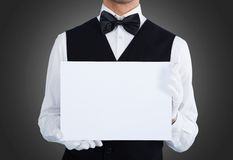 Midsection of waiter holding blank billboard. Over gray background royalty free stock image