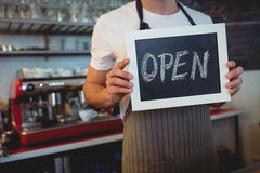 Midsection of waiter holding chalkboard at cafe Stock Image