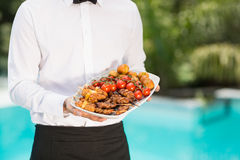 Midsection of waiter holding food tray Stock Photo