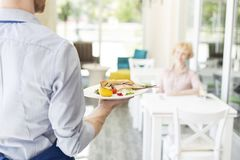 Midsection of waiter serving lunch to mature customer sitting at table in restaurant stock photography