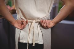 Midsection of waiter tying apron at coffee shop Stock Photos
