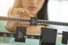 Midsection Of Woman Adjusting Weight Scale. Midsection of mid adult Asian woman adjusting balance weight scale royalty free stock image