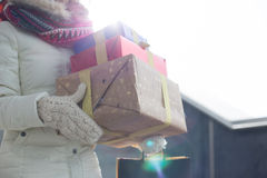 Midsection of woman carrying stacked gifts during winter by window Royalty Free Stock Images
