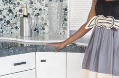 Midsection of woman with champagne set on kitchen counter Royalty Free Stock Photography
