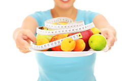 Midsection of a woman holding fruits and tape measure Royalty Free Stock Images