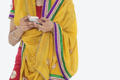 Midsection of woman in Indian clothing using cell phone over white background Royalty Free Stock Photography