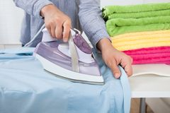 Midsection of woman ironing shirt Royalty Free Stock Image