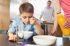 Midsection of woman with juice bottle standing by son having breakfast with man in background. Midsection of women with juice bottle standing by son having Stock Image