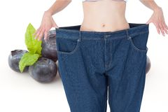 Midsection of woman in loose jeans by blueberries representing weight loss concept Royalty Free Stock Images