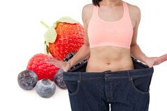 Midsection of woman in loose jeans by fruits representing weight loss concept Stock Photo