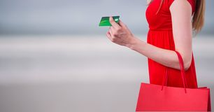 Midsection of woman with purse holding credit card against blurred background Royalty Free Stock Photography