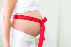 Midsection of woman with red ribbon on abdomen. Midsection of woman with red ribbon wrapped on pregnant abdomen stock photography