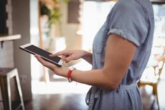 Midsection of woman scrolling digital tablet Stock Images