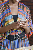 Midsection of woman in traditional African print attire using cell phone Royalty Free Stock Photos
