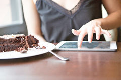 Midsection of woman using tablet PC by pastry in cafe. Midsection of women using tablet PC by pastry in cafe Stock Image