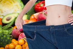 Midsection of woman wearing loose jeans with fruits and vegetable in background representing weight Stock Photos