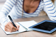 Midsection of woman writing in notebook by digital tablet Royalty Free Stock Photos