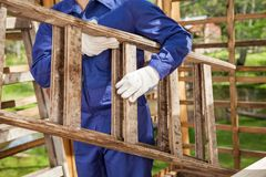 Midsection Of Worker Carrying Ladder. At construction site Stock Photo