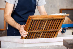 Midsection Of Worker Dipping Mold In Pulp And Stock Photography