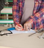 Midsection Of Worker Drawing Blueprint Stock Photography