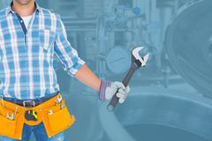 Midsection of worker holding wrench while standing against in factory. Digital composite of Midsection of worker holding wrench while standing against in factory Stock Photography