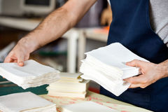 Midsection Of Worker Stacking Papers In Factory Royalty Free Stock Photography