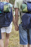 Midsection of young backpackers holding hands in countryside Royalty Free Stock Images