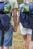 Midsection of young backpackers holding hands in countryside Stock Photo