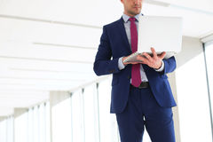 Midsection of young businessman using laptop while standing in new office Stock Photo