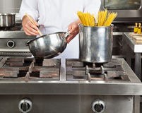 Chef Cooking Spaghetti. Midsection of young chef cooking spaghetti in commercial kitchen stock images