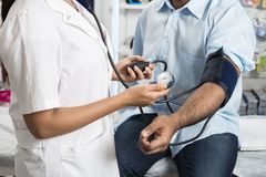 Doctor Holding Dial While Measuring Man`s Blood Pressure royalty free stock photos