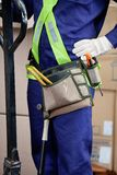 Midsection Of Young Foreman In Protective Wear. Midsection of male using pallet jack in warehouse Royalty Free Stock Images