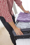 Midsection of young man unpacking suitcase in hotel room Royalty Free Stock Photo