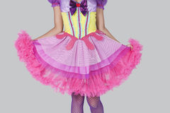 Midsection of young woman in doll's costume standing against gray background Stock Images