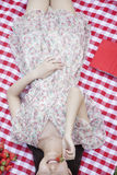 Midsection of a young woman lying on her back on a checkered blanket eating strawberries Royalty Free Stock Photos