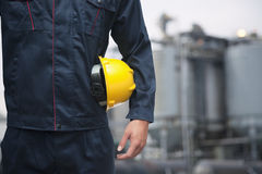 Midsection of young worker holding a yellow hardhat  outdoors with factory in the background Royalty Free Stock Image