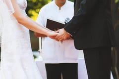 Midsectionen av den unga parhållhanden på bröllopceremoni arkivbilder
