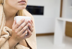 Midsectionen av hållande kaffe för den unga kvinnan rånar i hus Arkivfoton