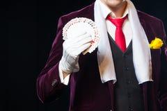 Midsectionen av trollkarlvisningen fläktade ut kort mot svart bakgrund Trollkarl jonglörman, rolig person, svart arkivfoton