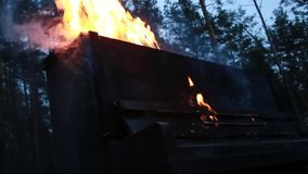 In the midst of forests is ablaze black piano, symbolism burning musical instrument.